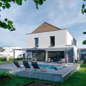 Construction à toiture audacieuse - façade arrière, piscine, jardin et terrasse
